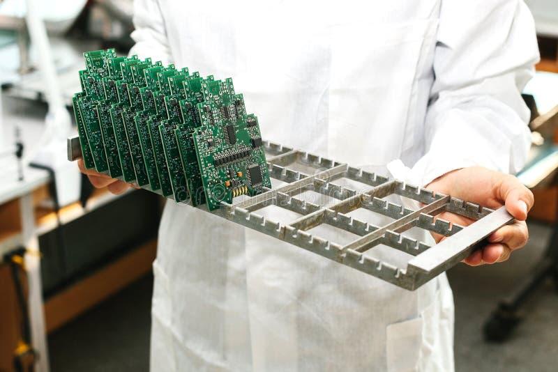 Τεχνικός με τον πίνακα κυκλωμάτων υπολογιστών με τα τσιπ Ανταλλακτικά και συστατικά για τον εξοπλισμό υπολογιστών Παραγωγή στοκ φωτογραφία με δικαίωμα ελεύθερης χρήσης