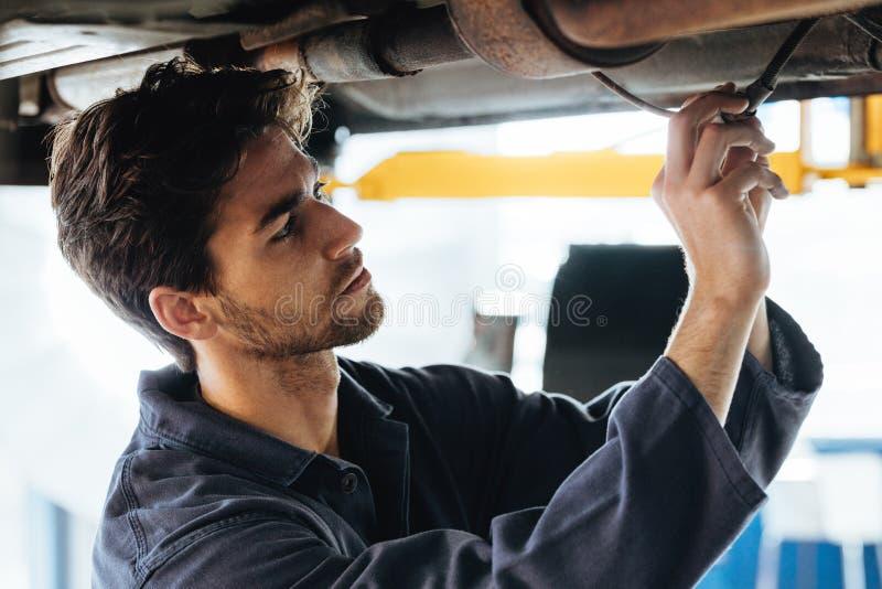 Τεχνικός που ελέγχει τα ηλεκτρικά καλώδια κάτω από το αυτοκίνητο στοκ εικόνα με δικαίωμα ελεύθερης χρήσης