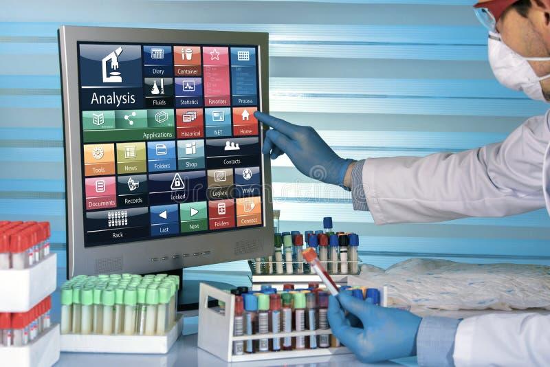 Τεχνικός που εργάζεται με τα αποτελέσματα δειγμάτων αίματος στον υπολογιστή μέσα στοκ εικόνα