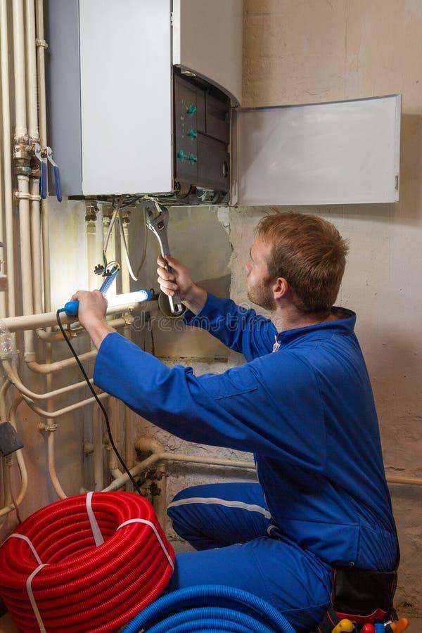 Τεχνικός που ελέγχει το σύστημα θέρμανσης στοκ εικόνες