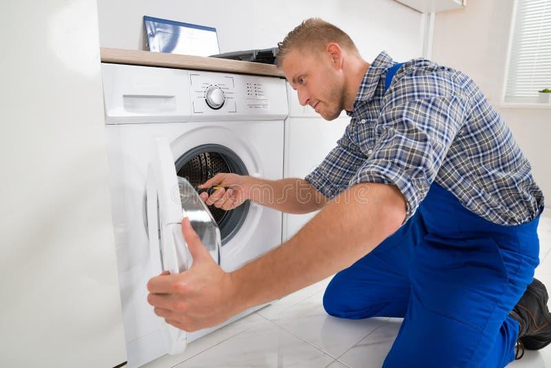 Τεχνικός που κατασκευάζει το πλυντήριο στοκ φωτογραφία