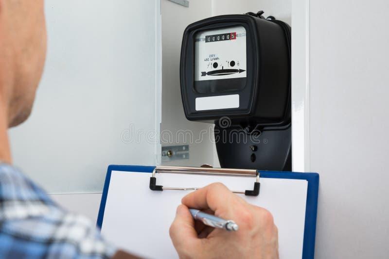 Τεχνικός που παίρνει την ανάγνωση του ηλεκτρικού μετρητή στοκ φωτογραφία με δικαίωμα ελεύθερης χρήσης