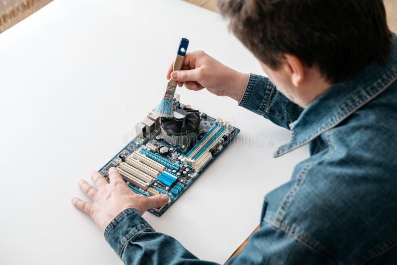 Τεχνικός που χρησιμοποιεί τη βούρτσα για τον καθαρισμό υπολογιστών στοκ εικόνες