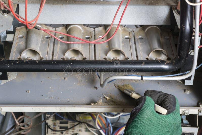 Τεχνικός που χρησιμοποιεί τη βούρτσα που καθαρίζει κάτω από τους καυστήρες στοκ φωτογραφία