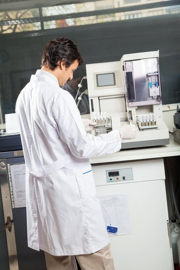 Τεχνικός που χρησιμοποιεί τη συσκευή ανάλυσης ούρων στο εργαστήριο στοκ εικόνα με δικαίωμα ελεύθερης χρήσης
