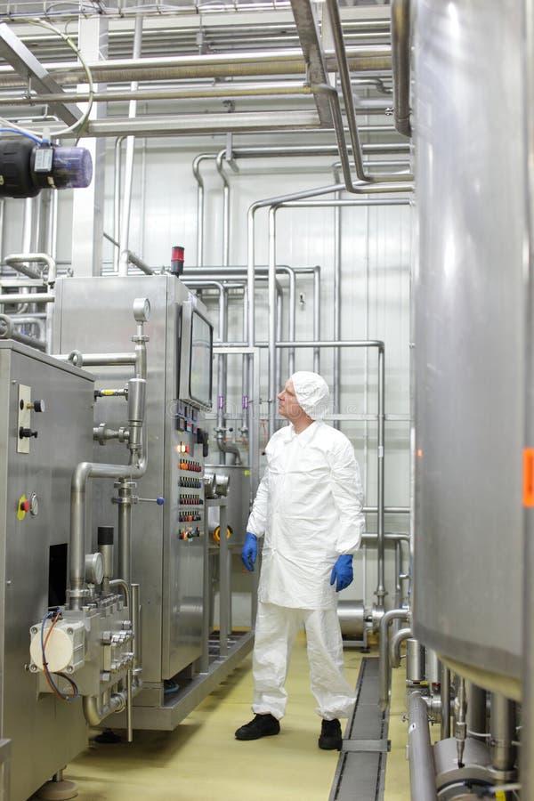 Τεχνικός στις άσπρες φόρμες και ΚΑΠ που ελέγχει τη βιομηχανική διαδικασία στις εγκαταστάσεις στοκ εικόνα με δικαίωμα ελεύθερης χρήσης