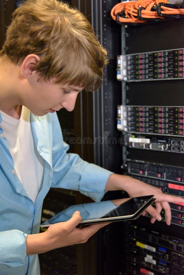 Τεχνικός ΤΠ που εργάζεται σε έναν κεντρικό υπολογιστή στοκ φωτογραφία