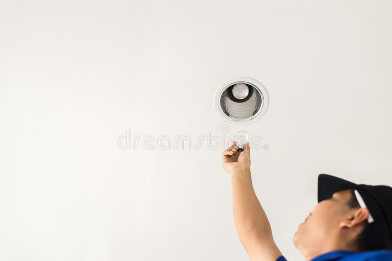 Τεχνικός χεριών που αλλάζουν με τη λάμπα φωτός λαμπτήρων των νέων οδηγήσεων, αποταμίευση δύναμης ηλεκτρική και έννοια αποδοτικότη στοκ φωτογραφίες