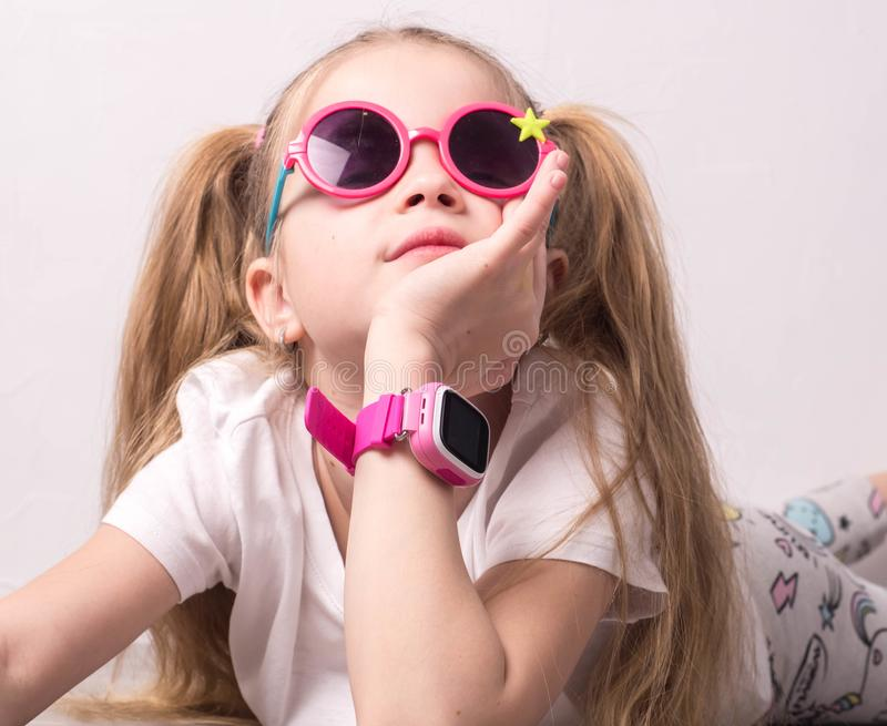 Τεχνολογία για τα παιδιά: ένα κορίτσι που φορά τα ρόδινα γυαλιά χρησιμοποιεί ένα smartwatch στοκ φωτογραφίες