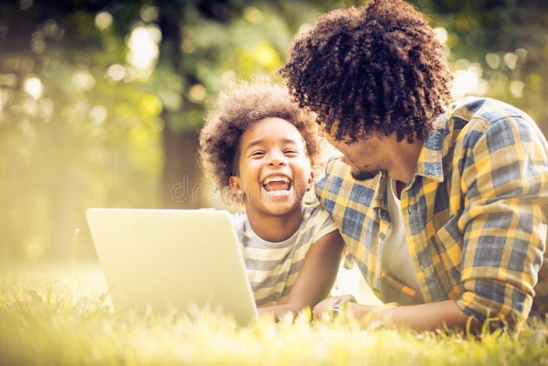 τεχνολογία συνεδρίασης φύσης ατόμων lap-top χλόης που χρησιμοποιεί τις νεολαίες στοκ εικόνες