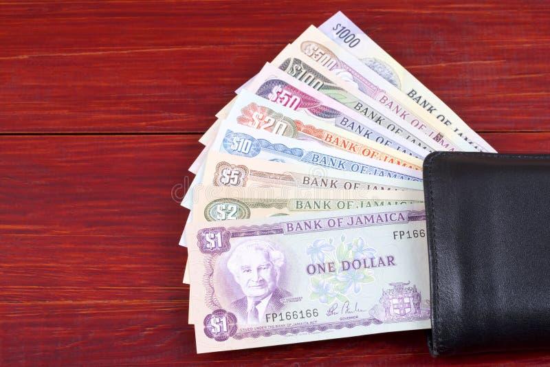 Τζαμαϊκανά χρήματα στο μαύρο πορτοφόλι στοκ φωτογραφίες
