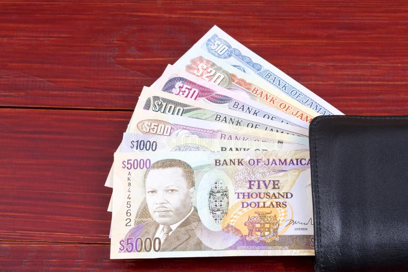 Τζαμαϊκανά χρήματα στο μαύρο πορτοφόλι στοκ φωτογραφίες με δικαίωμα ελεύθερης χρήσης