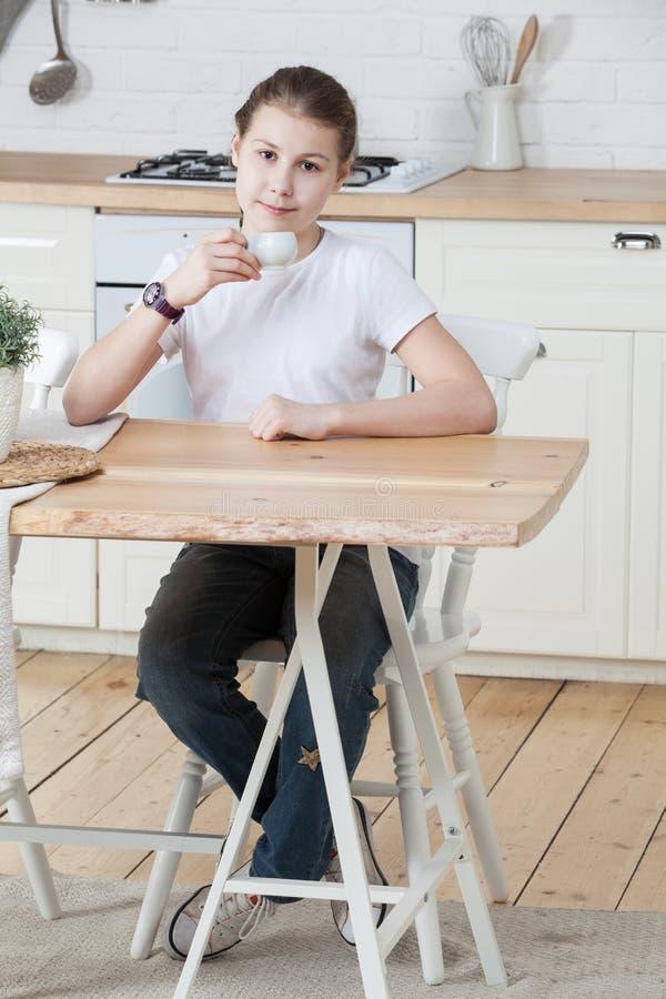 Τζιν παντελόνι επιδέσμου κοριτσιών και άσπρο τσάι κατανάλωσης μπλουζών από το φλυτζάνι καθμένος στον ξύλινο πίνακα σε μια κουζίνα στοκ εικόνες