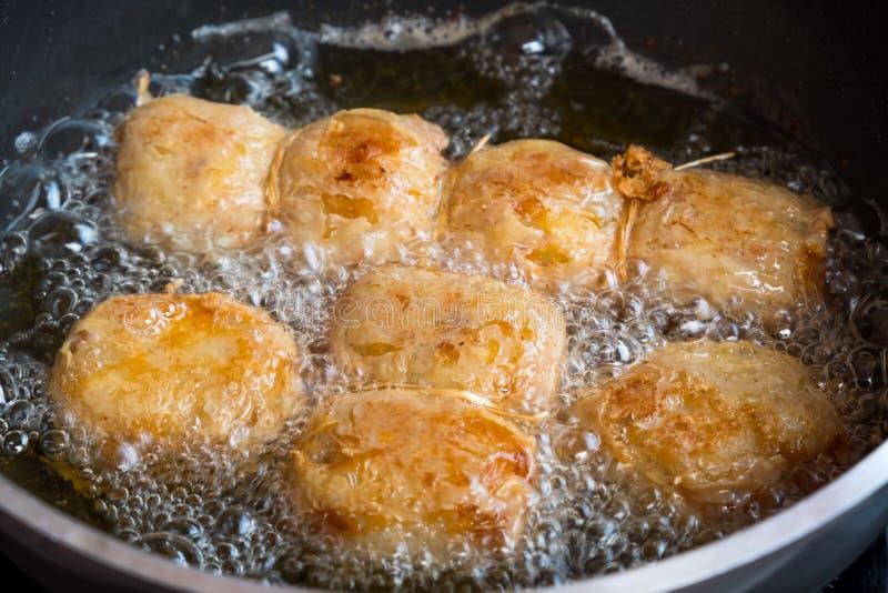 Τηγάνισμα ρόλων χοιρινού κρέατος στο τηγάνι στην κουζίνα είναι ανθυγειινά τρόφιμα που περιέχει πολλές από τη χοληστερόλη και το λ στοκ εικόνες