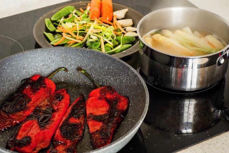 Τηγάνι και δοχείο με το λαχανικό στην κεραμική σόμπα στοκ εικόνα με δικαίωμα ελεύθερης χρήσης