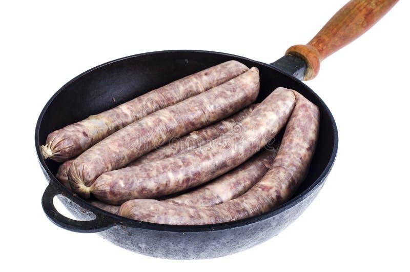 Τηγάνι με το ακατέργαστο σπιτικό λουκάνικο χοιρινού κρέατος στοκ εικόνα