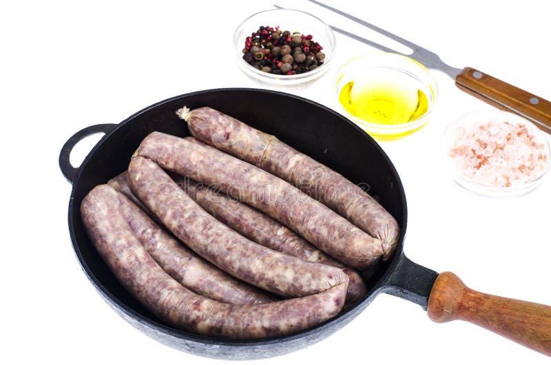 Τηγάνι με το ακατέργαστο σπιτικό λουκάνικο χοιρινού κρέατος στοκ φωτογραφία