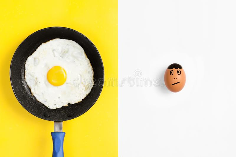 Τηγανίζοντας τηγάνι με το μαγειρευμένο αυγό και το ακατέργαστο συρμένο αυγό πρόσωπο που φαίνονται ανησυχημένα στοκ εικόνα με δικαίωμα ελεύθερης χρήσης