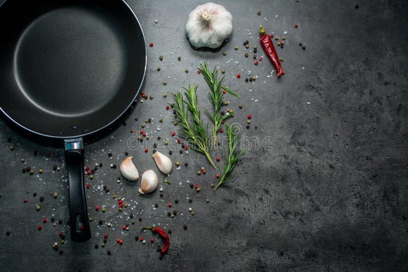 Τηγανίζοντας τηγάνι με το σκόρδο και πιπέρι στο μαύρο υπόβαθρο στοκ φωτογραφίες με δικαίωμα ελεύθερης χρήσης