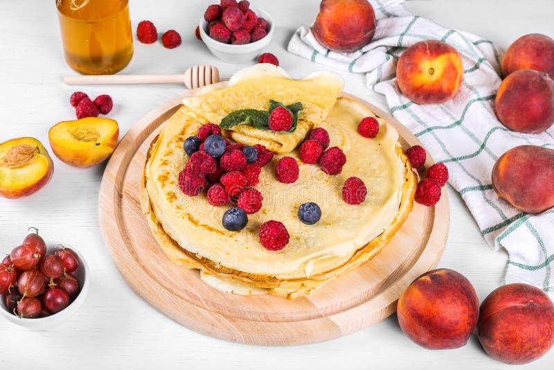 Τηγανίτες με τα σμέουρα και τα βακκίνια Υγιές θερινό πρόγευμα, σπιτικές κλασικές ρωσικές τηγανίτες, ελαφρύ υπόβαθρο πρωινού, στοκ εικόνες