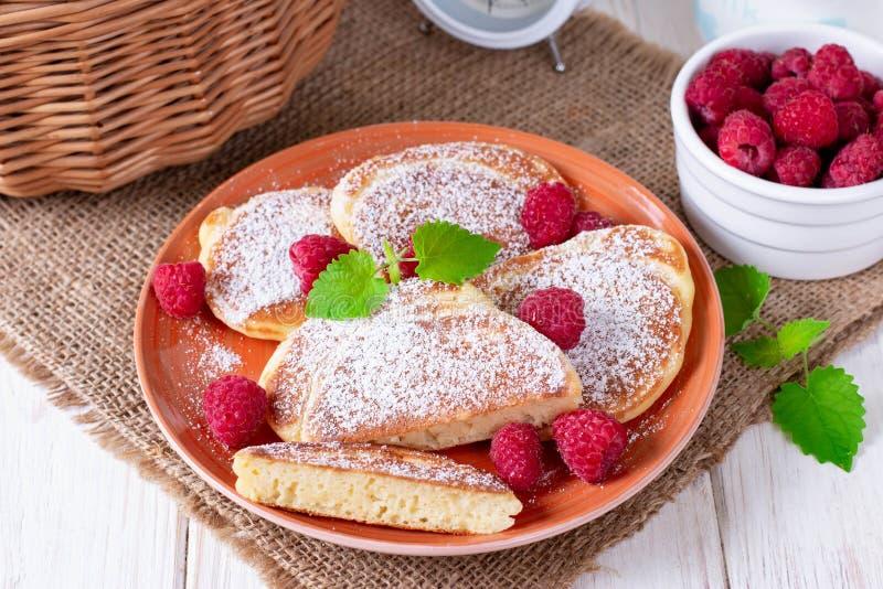 Τηγανίτες με την κονιοποιημένη ζάχαρη και τα φρέσκα σμέουρα στοκ εικόνες με δικαίωμα ελεύθερης χρήσης
