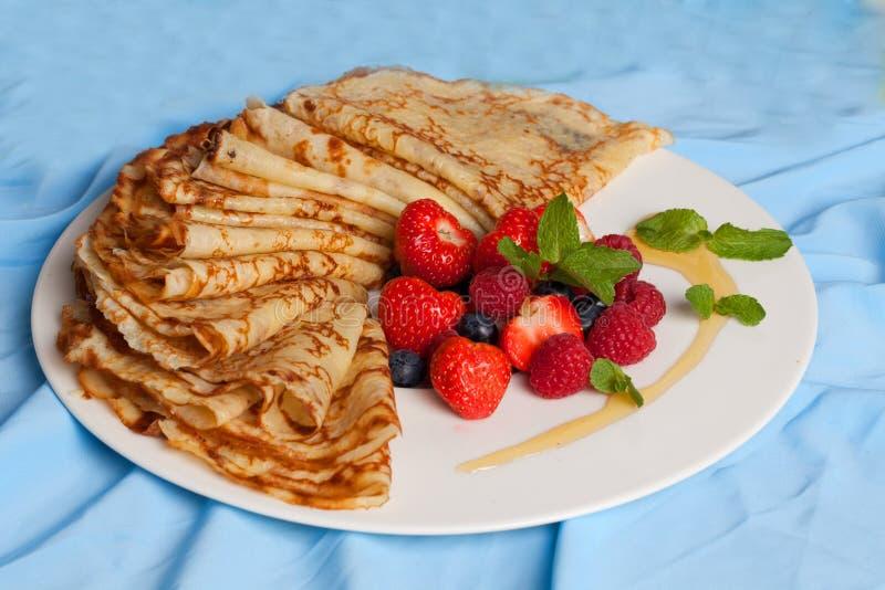 Τηγανίτες με το πιάτο μελιού μούρων στο μπλε πρόγευμα κέικ υφασμάτων στοκ εικόνα με δικαίωμα ελεύθερης χρήσης