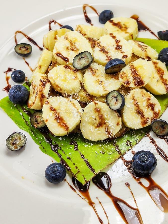 Τηγανίτες μπανανών με το σιρόπι και τα βακκίνια σοκολάτας στοκ εικόνες