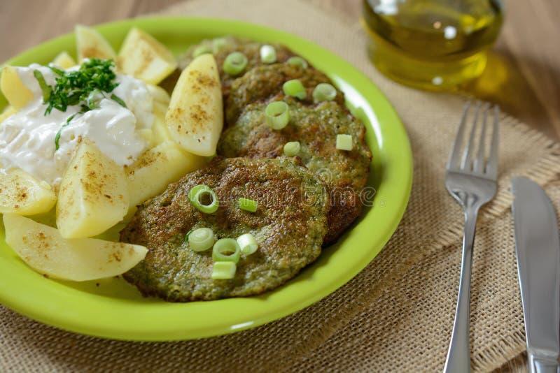 Τηγανίτες μπρόκολου με το κρεμμύδι, τις πατάτες και τον επίδεσμο στοκ εικόνες