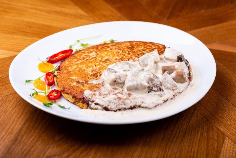 Τηγανίτες πατατών στην άσπρη σάλτσα μανιταριών Draniki - fritters πατατών τηγανίτες πατατών Το πιάτο naitonal της Λευκορωσίας στοκ φωτογραφίες
