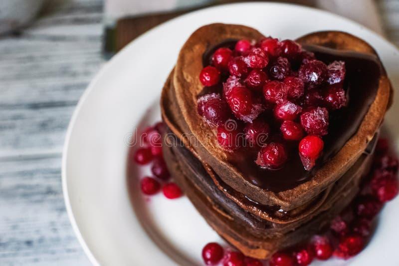 Τηγανίτες σοκολάτας με μορφή της καρδιάς, που χύνεται με την τήξη σοκολάτας και τα κόκκινα παγωμένα τα βακκίνια σε ένα άσπρο πιάτ στοκ εικόνα με δικαίωμα ελεύθερης χρήσης