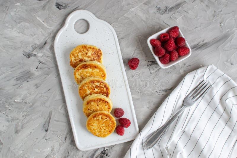 Τηγανίτες τυριών εξοχικών σπιτιών με τα σμέουρα, υγιές πρόγευμα στοκ εικόνες