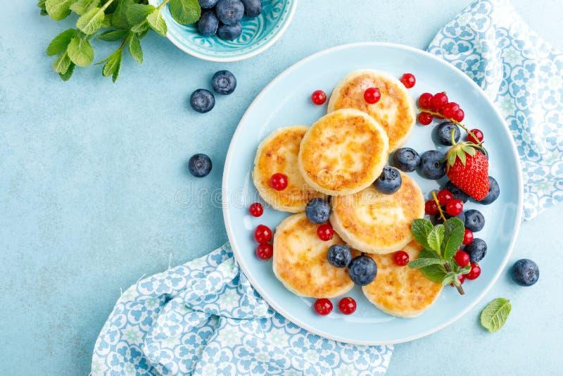 Τηγανίτες τυριών εξοχικών σπιτιών, syrniki με τα φρέσκα μούρα για το πρόγευμα στοκ εικόνα με δικαίωμα ελεύθερης χρήσης