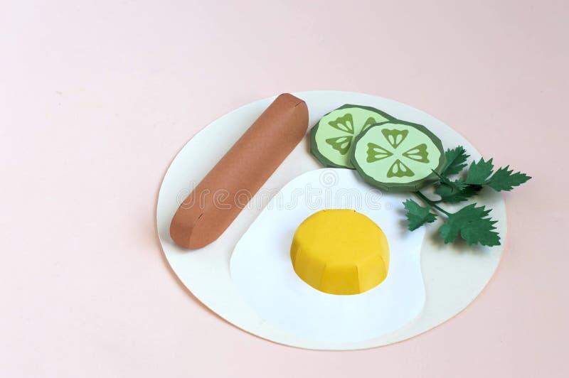 Τηγανισμένα έγγραφο αυγά με το λουκάνικο, τις φέτες αγγουριών και το μαϊντανό στο πιάτο στοκ φωτογραφία με δικαίωμα ελεύθερης χρήσης