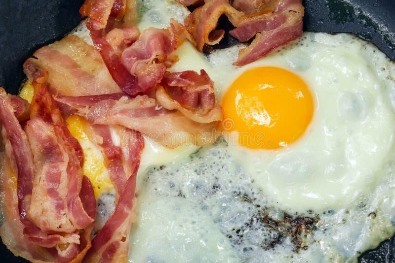 Τηγανισμένα αυγά για την κινηματογράφηση σε πρώτο πλάνο προγευμάτων με το μπέϊκον στοκ φωτογραφία με δικαίωμα ελεύθερης χρήσης