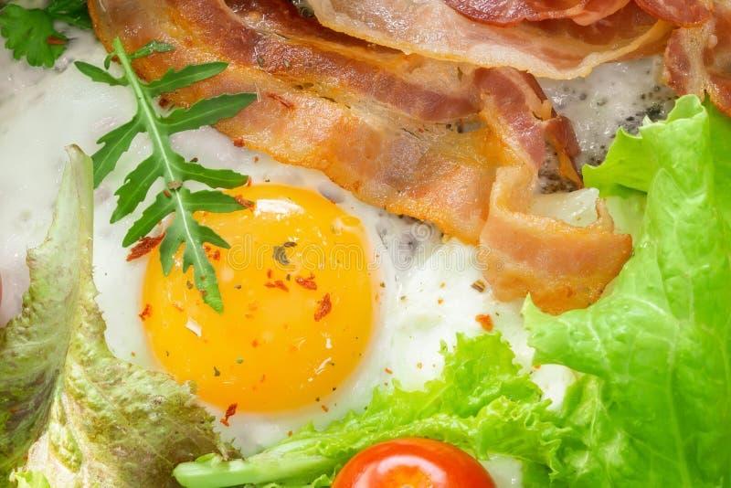 Τηγανισμένα αυγά για την κινηματογράφηση σε πρώτο πλάνο προγευμάτων με το μπέϊκον στοκ εικόνα με δικαίωμα ελεύθερης χρήσης