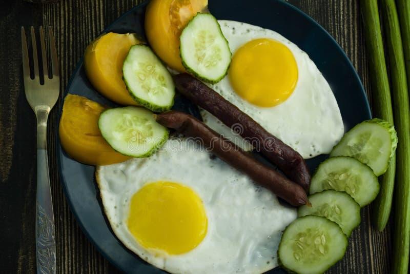 Τηγανισμένα αυγά και λουκάνικο σε ένα μπλε πιάτο πορσελάνης στοκ φωτογραφία με δικαίωμα ελεύθερης χρήσης