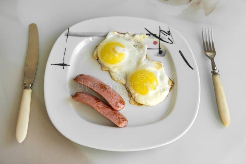 Τηγανισμένα αυγά με τα λουκάνικα σε ένα πιάτο, ένα μαχαίρι και ένα δίκρανο στοκ φωτογραφίες