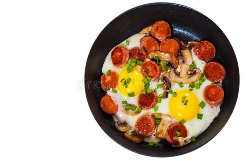 Τηγανισμένα αυγά με τα μανιτάρια και λουκάνικο σε ένα τηγανίζοντας τηγάνι Τοπ όψη απομονωμένος στοκ φωτογραφίες με δικαίωμα ελεύθερης χρήσης
