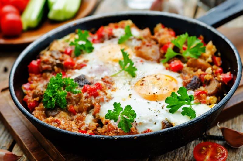 Τηγανισμένα αυγά με τα πιπέρια, τις ντομάτες, quinoa και τα μανιτάρια στοκ εικόνα