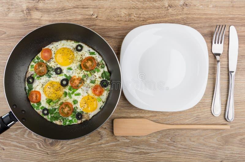 Τηγανισμένα αυγά με τα πράσινα, τις ντομάτες και τις ελιές στο τηγάνισμα του τηγανιού στοκ εικόνες