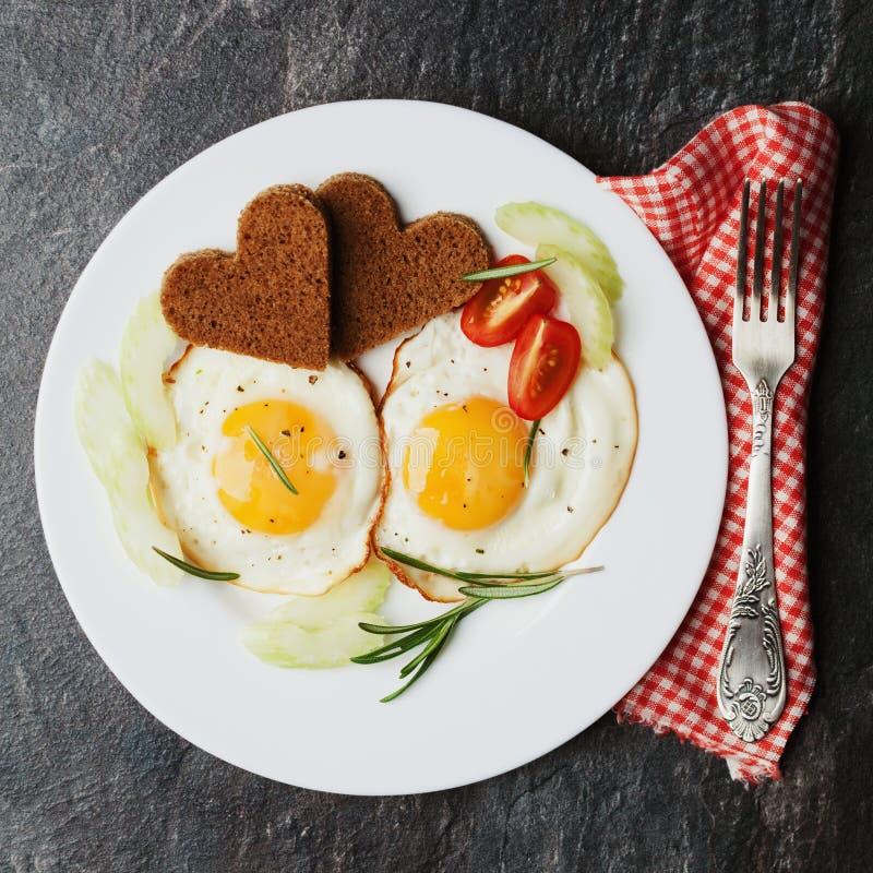 Τηγανισμένα αυγά με τα φρέσκα λαχανικά και φρυγανιά στη μορφή της καρδιάς στο άσπρο πιάτο στοκ φωτογραφίες