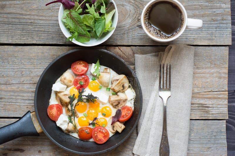 Τηγανισμένα αυγά σε ένα μαύρο τηγάνι με τα μανιτάρια και τις ντομάτες κερασιών στοκ εικόνα