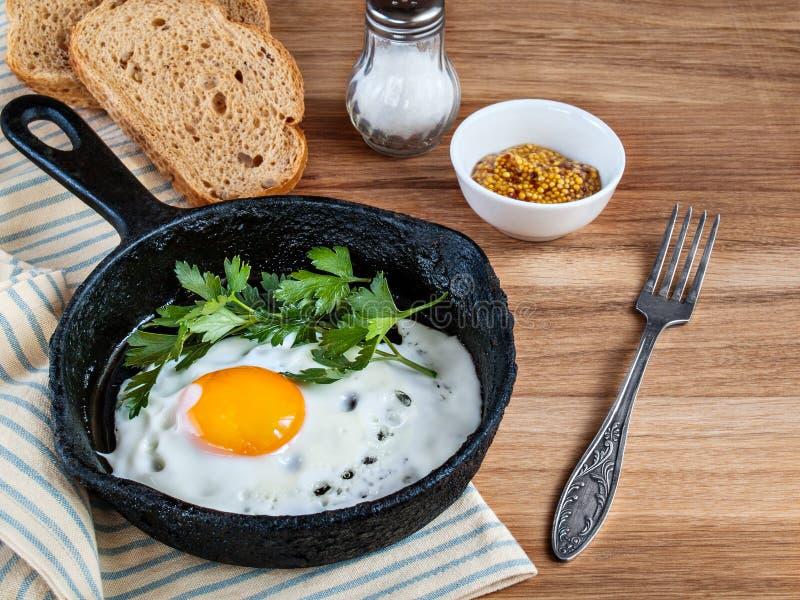 Τηγανισμένα αυγά σε ένα τηγάνι, ψωμί, άλας, δίκρανο στο ξύλινο υπόβαθρο στοκ φωτογραφίες