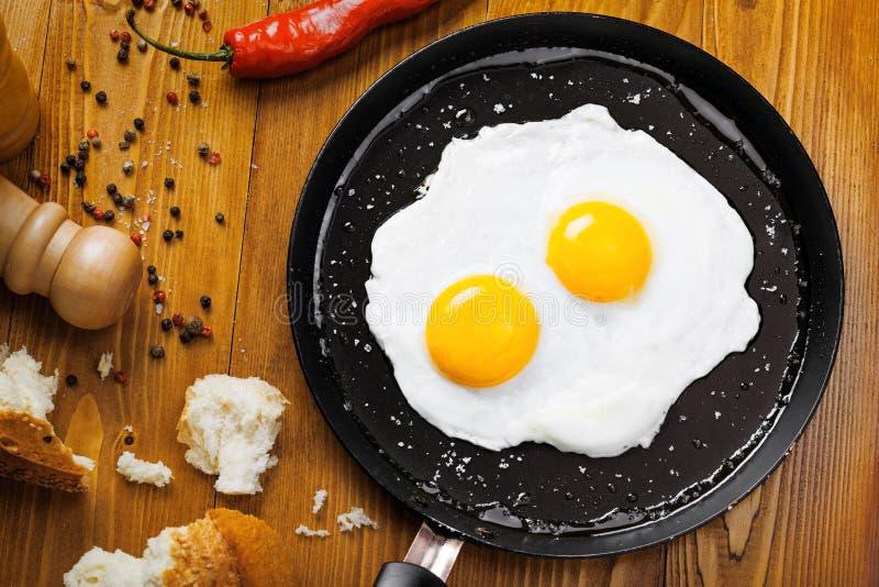 Τηγανισμένα αυγά σε ένα τηγάνι στοκ εικόνες