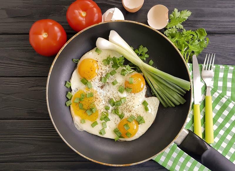 Τηγανισμένα αυγά σε ένα τηγανίζοντας τηγάνι, αγροτικά, πράσινα κρεμμύδια προγευμάτων δικράνων μαχαιριών, ντομάτα, μαύρο ξύλινο υπ στοκ εικόνα