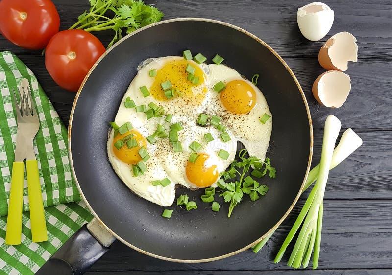 Τηγανισμένα αυγά στο τηγάνισμα του παν γεύματος, επιτραπέζια αγροτικά, πράσινα κρεμμύδια μαγείρων δικράνων μαχαιριών, ντομάτα, μα στοκ εικόνα με δικαίωμα ελεύθερης χρήσης