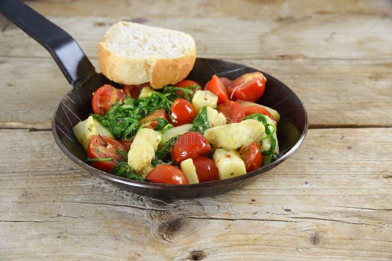 Τηγανισμένα λαχανικά σε ένα μαύρο τηγάνι με το σπαράγγι, τις ντομάτες και το spi στοκ φωτογραφίες με δικαίωμα ελεύθερης χρήσης
