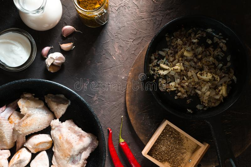 Τηγανισμένα κομμάτια κοτόπουλου σε ένα τηγανίζοντας τηγάνι, τα κρεμμύδια και το τσίλι Ινδικά τρόφιμα στοκ εικόνες