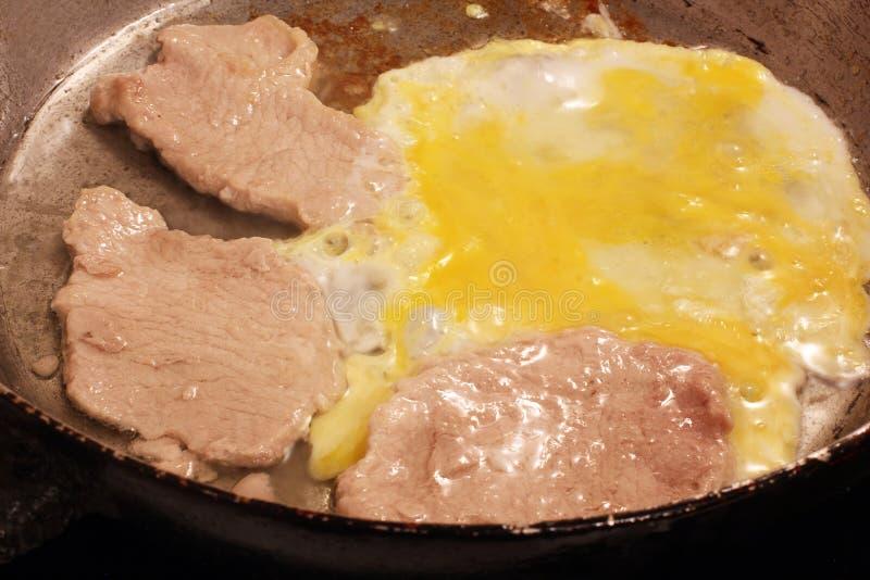 Τηγανισμένα κρέας και αυγό σε ένα skillet στοκ εικόνα