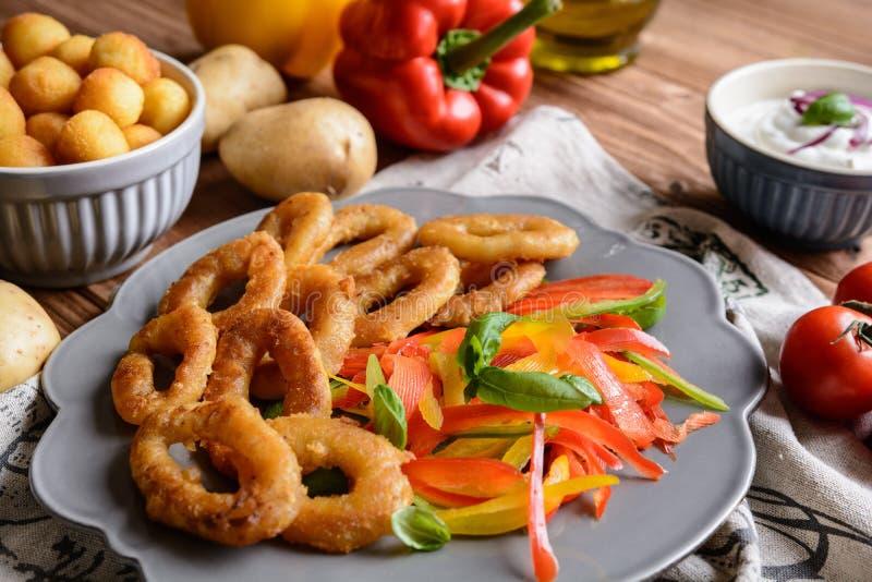 Τηγανισμένα κτύπημα δαχτυλίδια καλαμαριών με croquettes πατατών και τη σαλάτα πιπεριών στοκ εικόνες